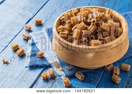 Raw pasta of buckwheat flour in a wooden bowl on blue wooden table. Gluten-free products. The source of vitamins and minerals. The concept of healthy and vegetarian food