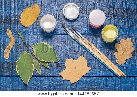 Gouache brushes and a variety of autumn leaves on a blue wooden table. Children's Art Project