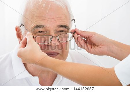 Close-up Of An Optician Helping Senior Male Patient With New Eyeglasses