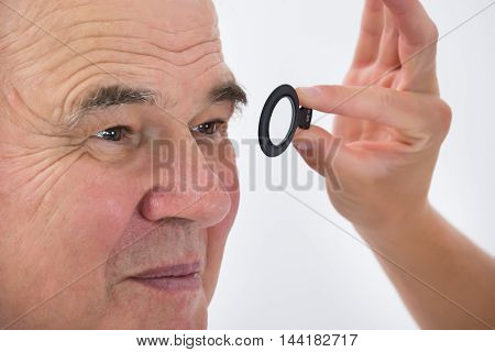 Close-up Of An Optometrist Examining Senior Male Patient's Eyesight With Trial Frame