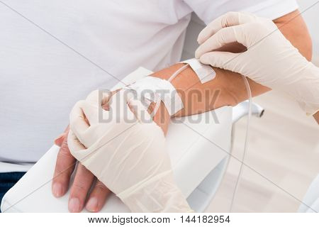 Close-up Of Doctor's Hand With Iv Drip Inserted In Patient's Hand