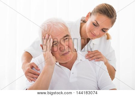 Young Female Doctor Consoling Sad Senior Male Patient