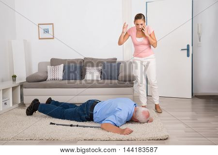 Shocked Young Woman Looking At Her Fainted Disabled Father Lying On Carpet