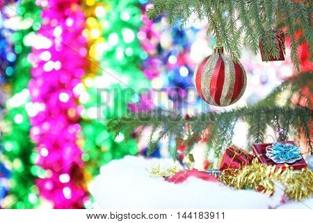 Closeup of red bauble hanging from a decorated Christmas tree