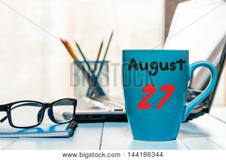 August 27th. Day 27 of month, morning coffee cup with calendar on workaholic workplace background. Summer time. Empty space for text.
