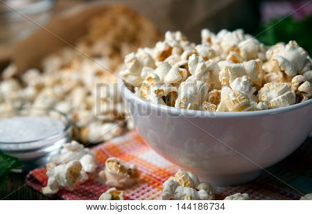 salted popcorn into a bowl on a napkin close up