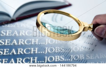inscription job search and a hand holding a magnifying glass close up