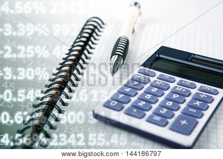 pen on a notebook and calculator and digits close up