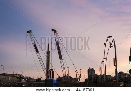 Cranes silhouettes of subway line over colorful sunset sky