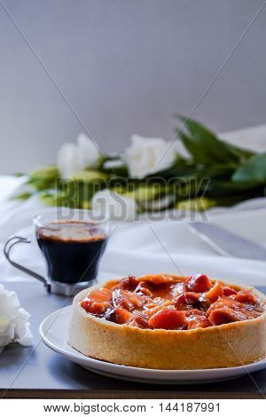 Summer peach and plum tart with caramel custard and a coffee glass cup. Free text background
