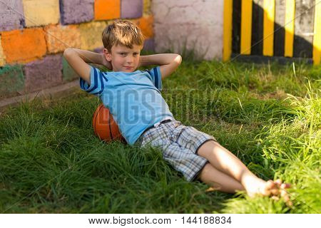 Boy With A Basketball Ball On The Grass