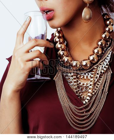 young african-american woman drinking champagne, holding glass, wearing lot of golden jewelry close up
