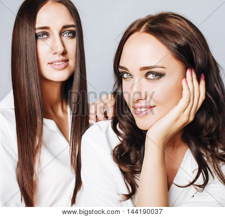 two sisters twins posing, making photo selfie, dressed same white shirt, diverse hairstyle friends close up