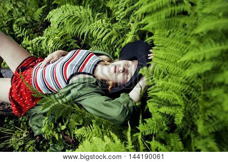 Pretty young blond girl hipster in hat among fern, vacation in green forest, lifestyle fashion people concept