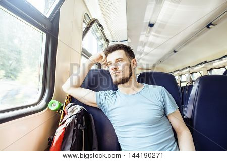 young pretty modern hipster guy traveller on train with skateboard alone, lifestyle vacation people concept close up