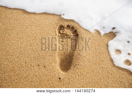 Footprint on the sand beach with motion blur foam of the sea