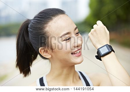young asian woman runner showing wearable fitness device (watch) and smiling.