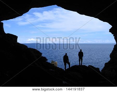 Silhouettes of two men overlooking a lake through the opening of a cave.