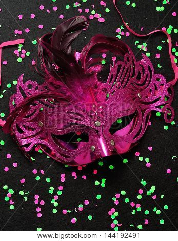 A mask isolated on a black background littered with pink and green confetti