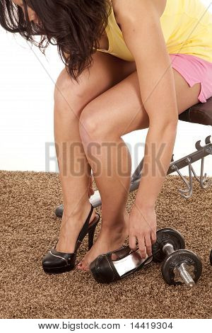 Woman Putting On Heels By Weights
