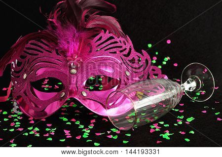 A mask isolated on a black background littered with pink and green confetti and a champagne glass. Shallow depth of field