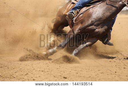 An up close barrel racing horse kicking up dirt.