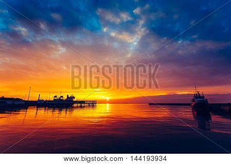 Harbor and boat at colorful sunset .