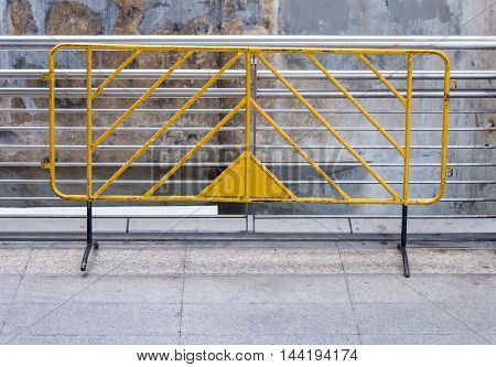Old yellow barrier near the sideway of the sky bridge.