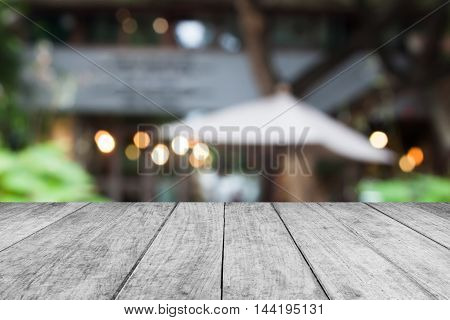 Black and white wooden table top with cafe blurred abstract background