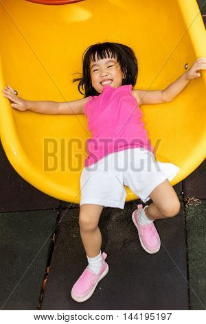 Asian Chinese Little Girl Sliding At Playground