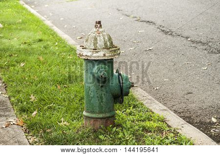 Classic weathered fire hydrant by pedestrian road