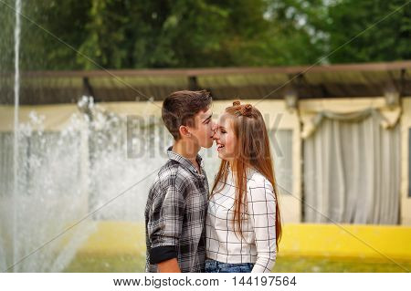 Enamoured teenagers fool around. Girlfriend and boyfriend strolling in a city park. Boy biting his girlfriend's nose. First love. He falls in love. Date.