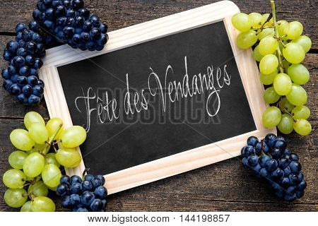 Blue And White Grapes With A Slate On Wooden Table