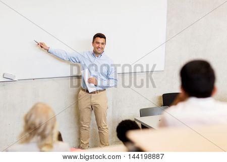 education, high school, university, teaching and people concept - group of students and teacher with marker standing at white board on lecture