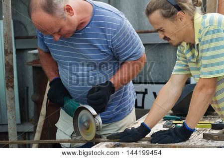 Master and assistant slicing metal section with angle grinder