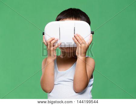 Little boy watching though virtual reality device