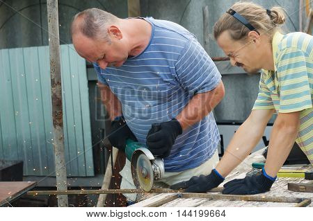 Workers cutting metal section with angle grinder with sparks