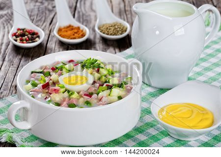 meat greens and vegetables cold summer soup with serum and yogurt sprinkled with parsley and spting onion in white cup with spices and mustard in gravy boat on old rustic boards view from above close-up