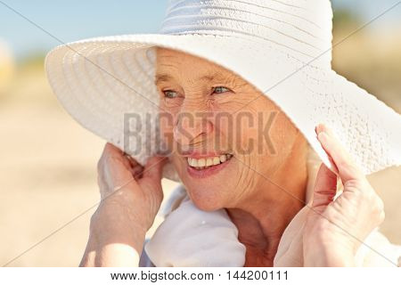 age, leisure and people concept - close up of happy senior woman in sun hat on summer beach