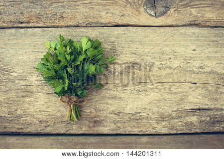 Bunch fresh parsley on old wooden background. Toned image.