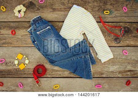 Children's clothing and accessories: jeans, jacket, hair clips, necklace and bracelet on old wooden background.