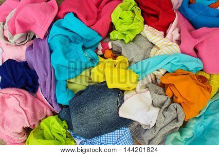 Closeup pile of carelessly scattered colorful clothes.