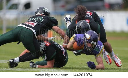 VIENNA, AUSTRIA - MAY 31, 2015: LB Ramon Azim (#25 Dragons) tackles WR Dominik Bundschuh (#3 Vikings) in a game of the Austrian Football League.