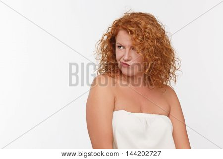 Portrait of doubtful mature woman looking away while posing in studio. Red haired lady in white dress posing isolated on white background.