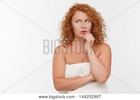 Portrait of doubtful mature woman touching her lips isolated on white background. Beautiful lady in white dress looking away. Emotions concept.