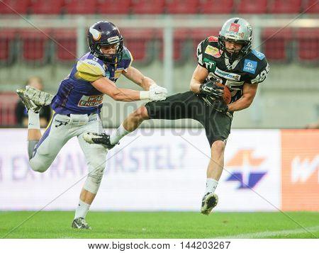 KLAGENFURT, AUSTRIA - JULY 11, 2015: DB Christoph Gombkoetoe (#9 Vikings) tackles WR Julian Ebner (#85 Raiders) in a game of the Austrian Football League.