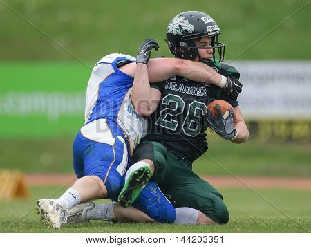 VIENNA, AUSTRIA - MAY 3, 2015: LB Marco Zoechner (#6 Giants) tackles RB Manuel Chytilek (#26 Dragons) in a game of the Austrian Football League.
