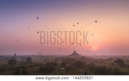Bagan pagoda field in morning soft light. Hot air balloons floating above Bagan pagoda sea in dreamlike misty morning in Mandaylay, Myanmar. Bagan is one of the most popular tourist destinations in Myanmar.