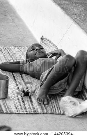 KARA, TOGO - MAR 9, 2013: Unidentified Togolese boy takes a rest on the ground. Children in Togo suffer of poverty due to the unstable econimic situation