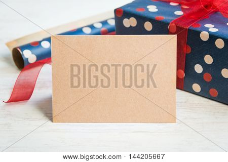 Empty greeting kraft card. Wrapped gift and wrapping materials over a white wood background.